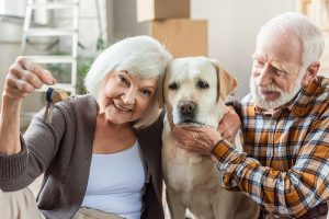 Man Petting Dog While Wife Holding Keys, Moving Concept