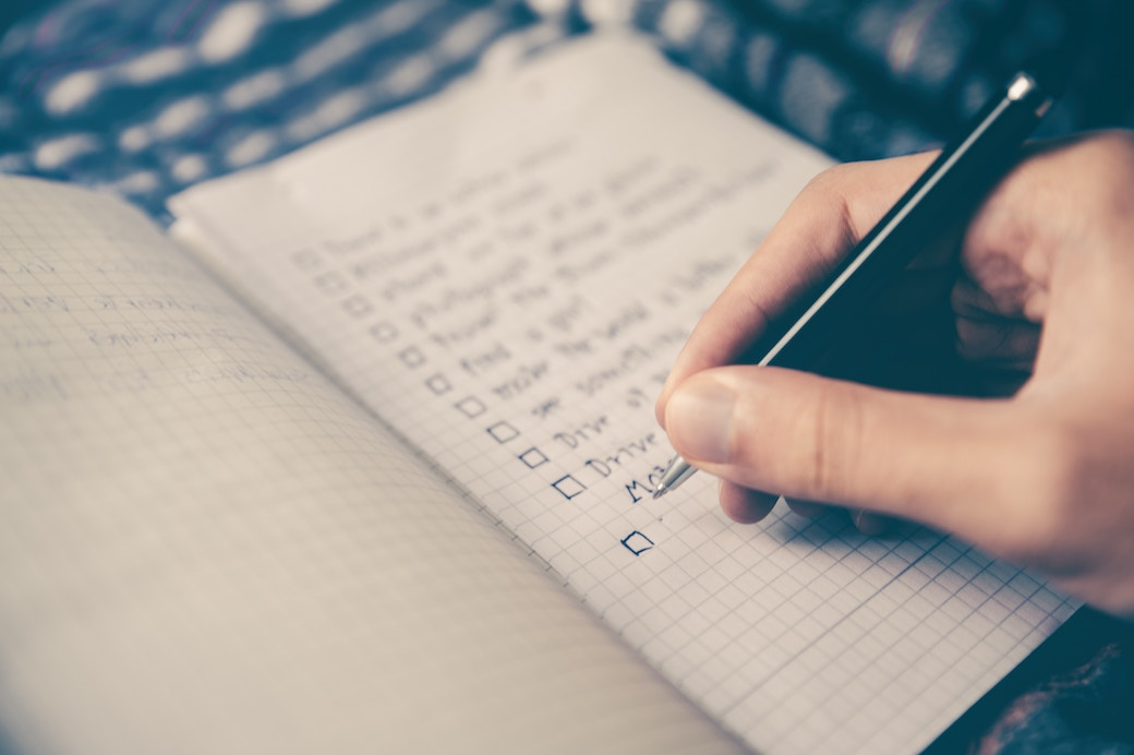 A person making a checklist before moving into a new house
